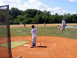 Players play baseball at camp