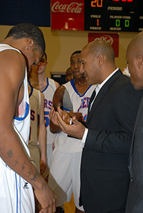 Coach Jay Price and players huddle during a game