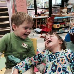 Honors program staff member Amanda Bennett's two children laugh in the child development center