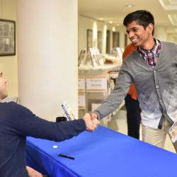 Two students and Global Scholars shake hands