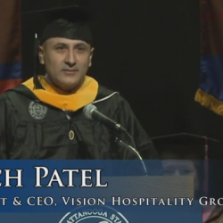 Commencement speaker Mitch Patel in cap and gown at podium, President & CEO of Vision Hospitality
