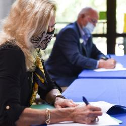 woman and man at table signing agreement
