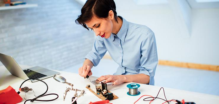 Engineer assembling electronic parts and components at her desk