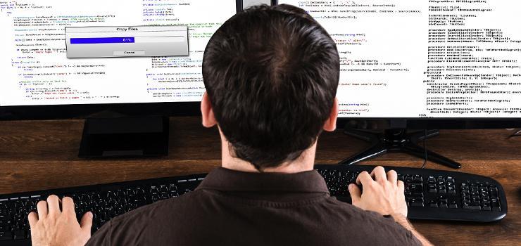 student programming on dual screens